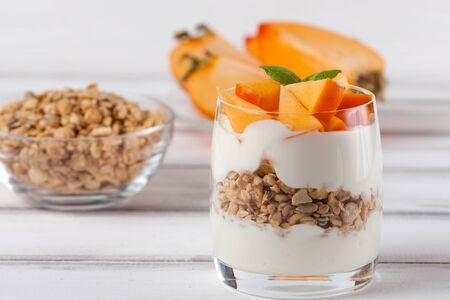 Persimmon creamy trifle in beautiful glasses, fresh ripe fruit slices on white wooden background. Healthy vegetarian food. Delicious dessert. Close up photography. Selective focus. Horizontal banner.