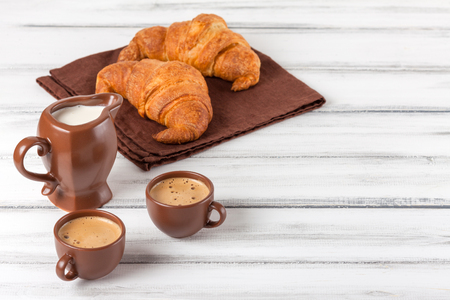 Freshly baked croissants on brown napkin, cream, to cups of coffee in ceramic dishes on white wooden background. Fresh pastries for breakfast. Delicious dessert. Closeup photography. Horizontal banner