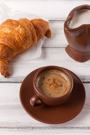 Freshly baked croissants on brown napkin, cream, to cups of coffee in ceramic dishes on white wooden background. Fresh pastries for breakfast. Delicious dessert. Closeup photography. Vertical banner. Banque d'images