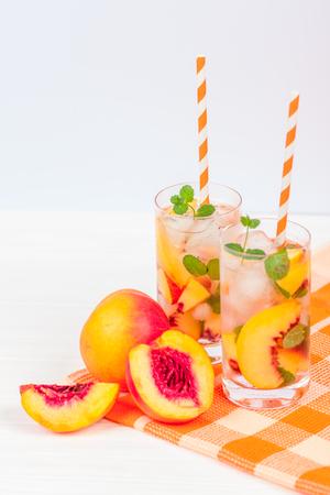 얼음과 민트 잎 복숭아 레모네이드. 흰색과 오렌지 익은 익은 천도 복숭아의 집에서 만드는 레모네이드. 복숭아 차 두 잔입니다. 상쾌한 여름 음료입니