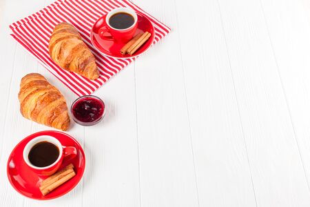 Freshly baked croissant on napkin, jam, cup of coffee in red cup on white wooden background. French breakfast. Fresh pastries for breakfast. Delicious dessert. Closeup photography. Horizontal banner. Zdjęcie Seryjne