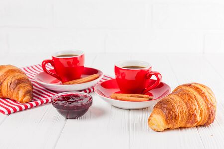 Freshly baked croissant on napkin, jam, cup of coffee in red cup on white wooden background. French breakfast. Fresh pastries for breakfast. Delicious dessert. Closeup photography. Horizontal banner. Banque d'images
