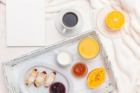 Freshly baked croissant, orange juice, jam, cup of black coffee on white wooden tray on plaid. Homemade cookie. Fresh pastries for breakfast. Delicious dessert. Closeup photography. Horizontal banner. Banque d'images