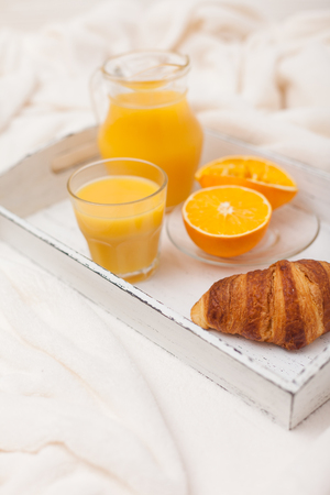 Freshly baked croissant, orange juice, jam, cup of black coffee on white wooden tray on plaid. Homemade cookie. Fresh pastries for breakfast. Delicious dessert. Closeup photography. Vertical banner.