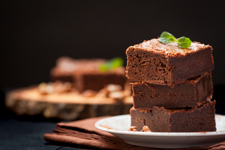 Chocolate brownie square pieces in stack on white plate with walnuts, decorated with mint leaves and cocoa on black background. Delicious dessert. Dark mood. Close up photography. Selective focus. Stock Photo - 93692827