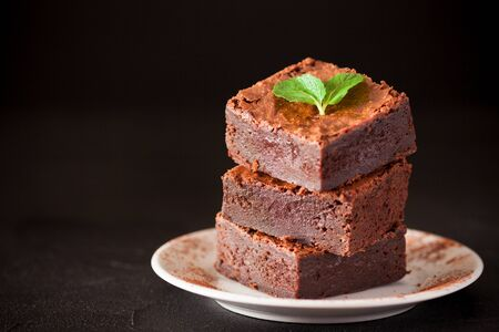 Chocolate brownie square pieces in stack on white plate with walnuts, decorated with mint leaves and cocoa on black background. Delicious dessert. Dark mood. Close up photography. Selective focus.