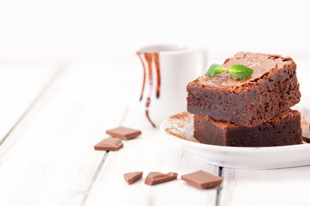 Chocolate brownie square pieces in stack on white plate decorated with mint leaves and cocoa powder on white vintage wooden background. American traditional delicious dessert. Close up photography.