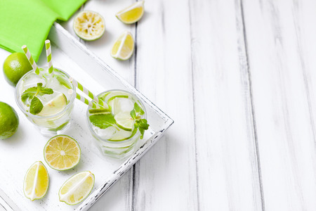 Caipirinha, mojito cocktail with lime, brown sugar, ice and mint leaves in beautiful glasses, cut green citrus on white wooden background. Summer alcohol drink. Close up photography. Selective focus.