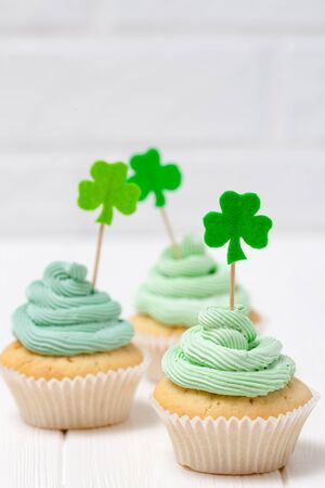 St. Patricks Day theme colorful vertical banner. Cupcakes decorated with green buttercream and craft felt decorations in form of shamrock leaves on white background. Copy space. For greeting card. Stock Photo