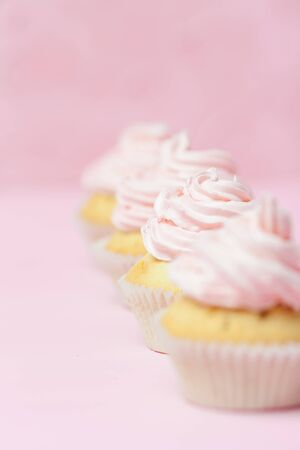 Cupcake decorated with pink buttercream on pastel pink background. Sweet beautiful cake. Vertical banner, greeting card for birthday, wedding, women's day. Close up photography. Selective focus.