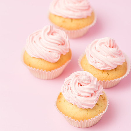 Cupcake decorated with pink buttercream on pastel pink background. Sweet beautiful cake. Square banner, greeting card for birthday, wedding, women's day. Close up photography. Selective focus.