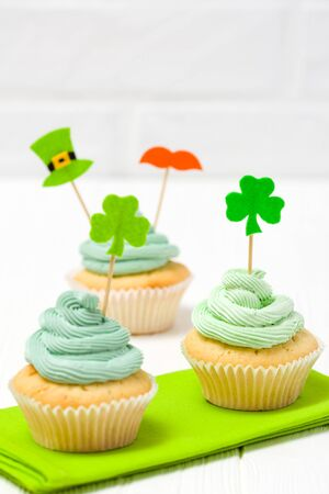 St. Patrick's Day theme colorful vertical banner. Cupcakes decorated with green buttercream and craft felt decorations in form of shamrock leaves on white background. Copy space. For greeting card. Imagens