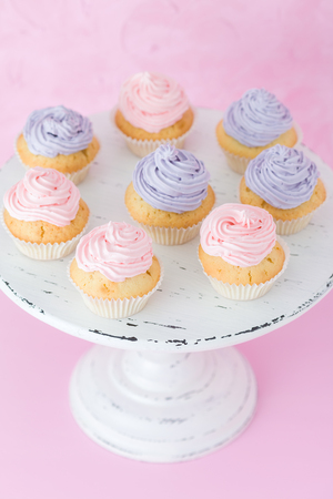 Violet and pink cupcakes with cream on white shabby shic stand on pastel pink background. Sweet beautiful decorated cakes. Horizontal banner or greeting card for birthday wedding mothers day.