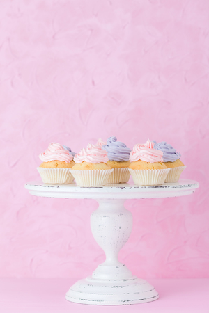 Cupcakes with pink and violet cream on white shabby shic stand on pastel pink background. Sweet beautiful decorated cake. Horizontal banner or greeting card for birthday wedding mothers day.