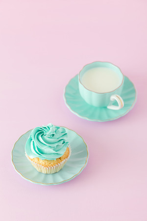 Cupcake with mint cream decoration and cup of milk on pink pastel background with copy space - mothers day vertical banner, congratulation, greeting card for birthday, romantic wedding invitation. Imagens