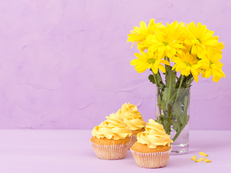Yellow chrysanthemum in glass and sweet cupcake with yellow cream on violet pastel background - mothers day layout design with flowers, greeting card for birthday, wedding, valentine or women day. Stock Photo