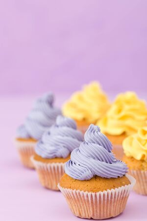 Cupcakes decorated with yellow cream on violet pastel background. Copyspace area. Can be used for greeting, mothers days and valentines card. Minimalism concept.