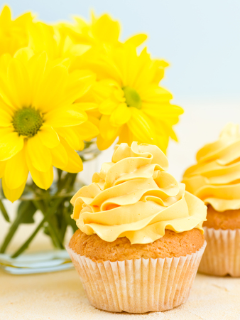 Cupcake with yellow cream decoration and bouquet of yellow chrysanthemum in glass on blue and yellow pastel background: congratulation poster, greeting card for birthday or wedding