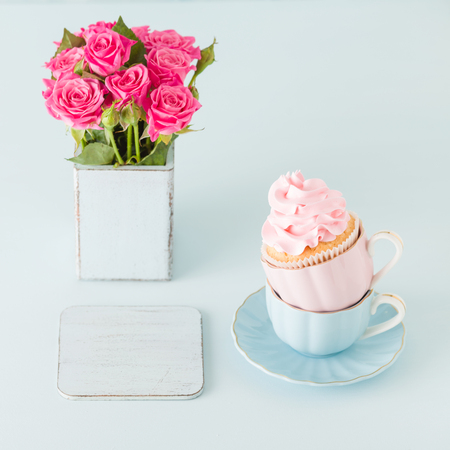 Cupcake with gentle pink cream decoration in two cups on blue pastel background - banner for wedding or birthday party invitation, congratulation card, valentine or mothers day.