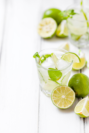 Summer refreshing cocktail caipirinha with lime and mint on white wooden vintage background. Fresh summertime iced drink with green citrus and fragrant leaves in beautiful glasses. Stock Photo