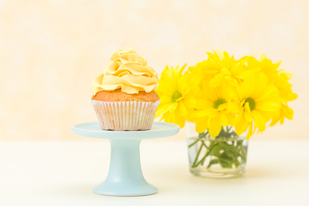Cupcake with tender yellow cream decoration on stand and bouquet of chrysanthemum in glass vase on pastel background. Sweet baked dessert for greeting card. Stock fotó