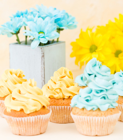 Yellow and blue chrysanthemum in retro shabby chic vase with cupcakes decorated with cream on pastel background. Sweet bakery for greeting card in minimalism still life concept.