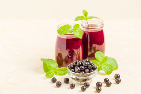 Currant smoothie decorated with fresh green mint leaves and raw ripe berries on yellow pastel background - transparent jars of summer blended vitamin cocktail for healthy food concept. Standard-Bild