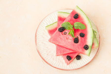 Watermelon slice pie with blackberries and mint leaf on pastel yellow background with copy space - close up macro photography of summer fresh raw ripe fruit for delicious vegetarian dessert.