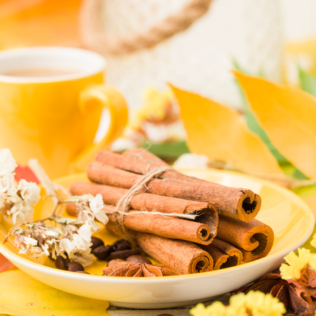 Autumn banner with cup of coffee with cinnamon on white wooden background with colorful tree leaves - multicolored foliage and dry flower with hot drink for seasonal natural design. Stock Photo