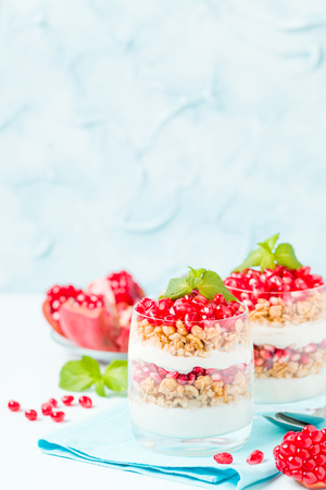 Pomegranate parfait - sweet organic layered dessert with granola flakes, yogurt and ripe fruit seeds in beautiful glasses on pastel blue background with copy space. Natural vegetarian healthy food. Stock Photo