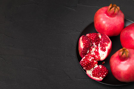 Ripe red pomegranate closeup photography on black background with copy space - seasonal raw whole and cut juicy fruit with seeds in dark mood style with empty space for text. 스톡 콘텐츠