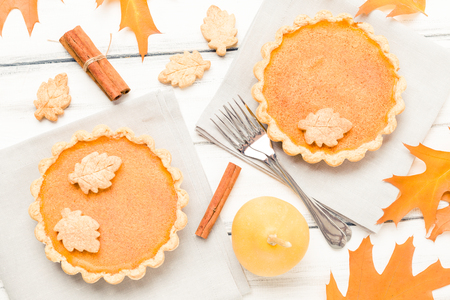 Pumpkin pie with cinnamon and cookies on gray napkins on white wooden background with autumn yellow leaves - top view close up photography of seasonal american traditional sweet baked food.