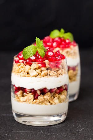 Pomegranate parfait - sweet organic layered dessert with granola flakes, yogurt and ripe fruit seeds in beautiful glasses on black background with copy space. Natural healthy food in dark mood style.