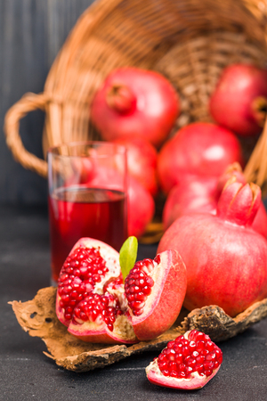 Ripe red pomegranates in wicker basket and seeds in spoon closeup photography on black Banque d'images