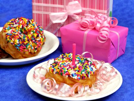Festive donuts with gifts, ribbons and birthday candle photo