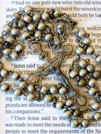 saint: Vintage Rosary Beads on Bible Page Stock Photo