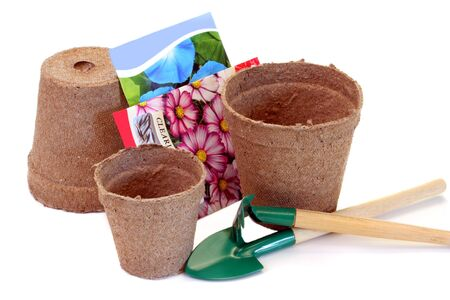 Peat pots with seeds and tools on white with copy space
