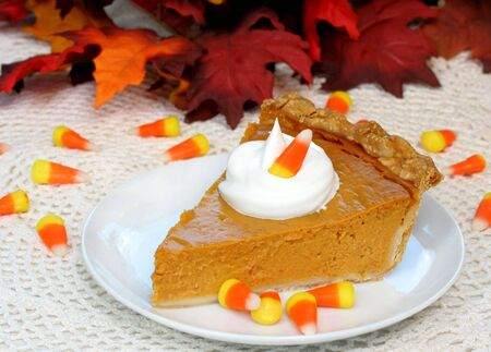 One slice of Pumpkin Pie with Candy Corn and Fall Leaves Stock Photo