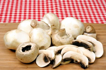 unwashed: Fresh Unwashed Mushrooms on Cutting Board