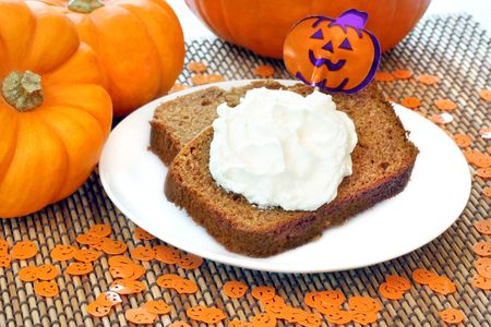 cake pick: Two slices of fresh pumpkin pound cake topped with whipped cream and a pumpkin pick.  Confetti pumpkins and pumpkins surround the plate.