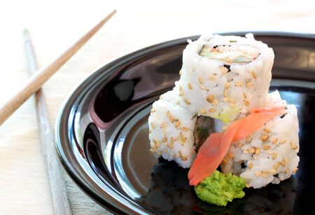 crabmeat: Three California Roll sushi stacked on a plate with fresh ginger and wasabi.