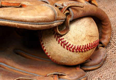 hardball: Well worn and used baseball in the pocket of a baseball mitt.