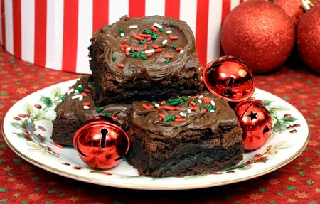 Chocolate frosted Christmas fudge brownies on a festive holiday plate.