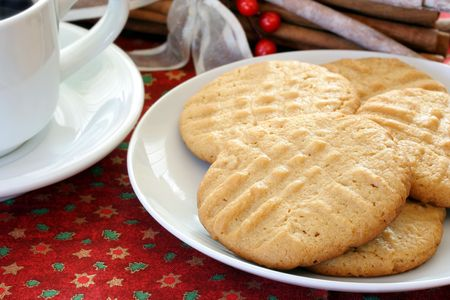 holiday cookies: Peanut butter cookies on a plate, close up, with coffee to the side on a Christmas tablecloth. Stock Photo