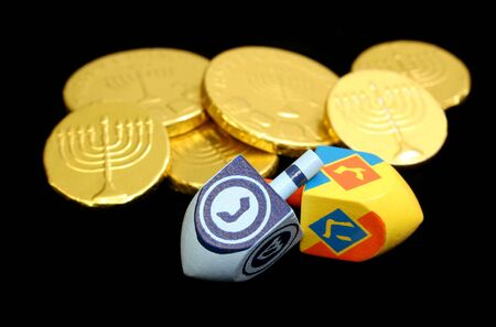 yiddish: Two dreidels in front of golden gelt. Stock Photo