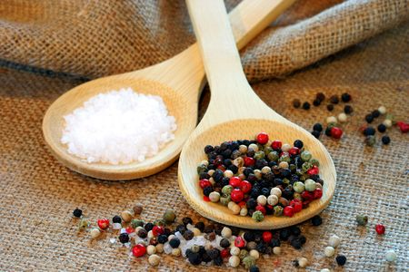 Two wooden spoons on burlap holding sea salt and mixed peppercorns. Stock Photo