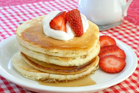 Fresh and homemade pancakes topped with cream and strawberries. Stock Photo - 4093103