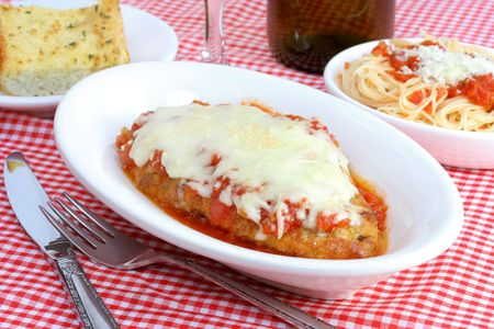 Chicken parmigiana with sides of spaghetti and garlic bread in individual plates.