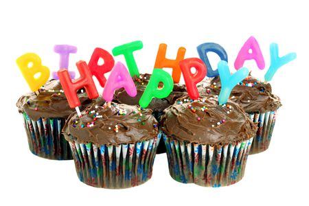 Five chocolate cupcakes with candles that spell out Happy Birthday, isolated on white.
