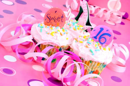 Two pink cupcakes with Sweet 16 on them in a pink feminine setting.